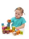 Menina que joga com blocos de madeira Imagens de Stock Royalty Free