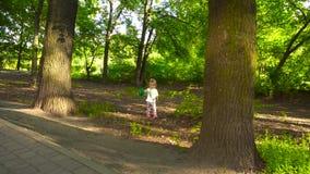 Menina que joga com a bola no parque vídeos de arquivo