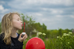 Menina que joga com bolhas de sabão Fotografia de Stock Royalty Free