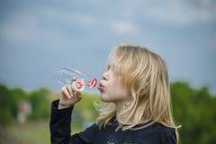 Menina que joga com bolhas de sabão Fotografia de Stock