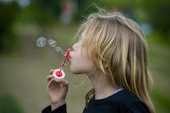 Menina que joga com bolhas de sabão Fotos de Stock Royalty Free