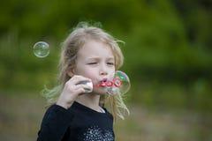 Menina que joga com bolhas de sabão Fotos de Stock