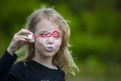 Menina que joga com bolhas de sabão Foto de Stock