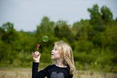 Menina que joga com bolhas de sabão Foto de Stock Royalty Free