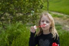 Menina que joga com bolhas de sabão Imagens de Stock