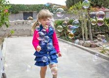 Menina que joga com bolhas de sabão no jardim foto de stock