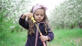 Menina que joga com bolhas de sab?o no jardim de floresc?ncia, movimento lento vídeos de arquivo