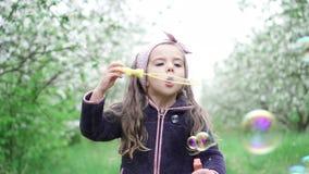Menina que joga com bolhas de sab?o no jardim de floresc?ncia, movimento lento filme