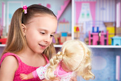 Menina que joga com boneca Imagens de Stock Royalty Free