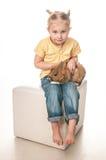 Menina que joga com coelhinho da Páscoa em um fundo branco Foto de Stock