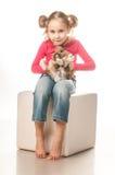 Menina que joga com coelhinho da Páscoa em um fundo branco Fotos de Stock