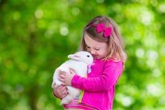 Menina que joga com coelho Fotografia de Stock