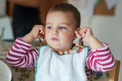 Menina que joga com a colar do ` s da mamã fotos de stock
