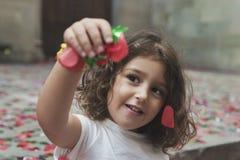 Menina que joga com confetes do partido de rua imagem de stock royalty free
