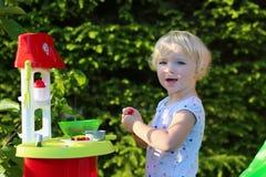 Menina que joga com cozinha do brinquedo fora imagens de stock