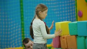 Menina que joga com cubos macios vídeos de arquivo