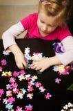 Menina que joga com enigma de serra de vaivém Fotos de Stock Royalty Free