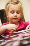 Menina que joga com enigma de serra de vaivém Fotografia de Stock Royalty Free