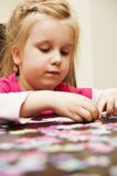 Menina que joga com enigma de serra de vaivém Imagem de Stock Royalty Free