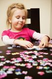 Menina que joga com enigma de serra de vaivém Imagens de Stock Royalty Free