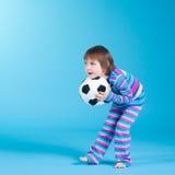 Menina que joga com esfera de futebol Foto de Stock