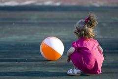 Menina que joga com esfera de praia Fotos de Stock