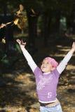 Menina que joga com folhas Imagens de Stock