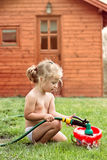 Menina que joga com mangueira e água Imagem de Stock