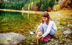 Menina que joga com o cachorrinho na costa do lago preto Foto de Stock