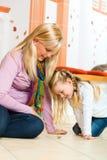 Menina que joga com o girador de madeira do brinquedo Fotografia de Stock