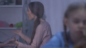 Menina que joga com o peluche-urso que confunde a atenção dos pais que têm o conflito video estoque