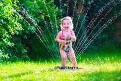 Menina que joga com o sistema de extinção de incêndios da água do jardim Fotografia de Stock