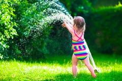 Menina que joga com o sistema de extinção de incêndios da água do jardim Imagem de Stock Royalty Free