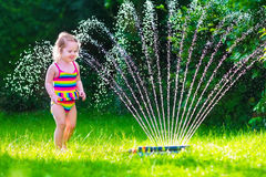 Menina que joga com o sistema de extinção de incêndios da água do jardim Imagem de Stock