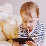 Menina que joga com o smartphone contra o fundo do urso de peluche Conceitos em mudança dos jogos e da apreciação entre crianças fotografia de stock royalty free