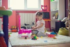 menina que joga com os brinquedos na sala de crianças Fotografia de Stock