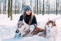 Menina que joga com os cães na neve Imagens de Stock Royalty Free