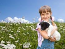 Menina que joga com puppiy pequeno Fotografia de Stock