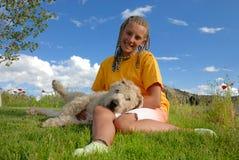 Menina que joga com seu cão Fotografia de Stock
