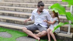 Menina que joga com seu pai Supõe que mão video estoque
