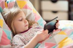 Menina que joga com a tabuleta na cama fotografia de stock