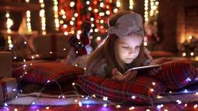 Menina que joga com tabuleta, smartphone perto da árvore de Natal vídeos de arquivo