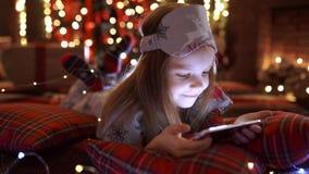 Menina que joga com tabuleta, smartphone perto da árvore de Natal video estoque