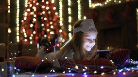 Menina que joga com tabuleta, smartphone perto da árvore de Natal filme