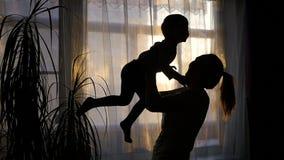 Menina que joga com um bebê perto da janela filme