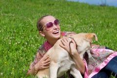 Menina que joga com um filhote de cachorro Foto de Stock