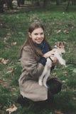 Menina que joga com um terrier de raposa do cão exterior Imagem de Stock