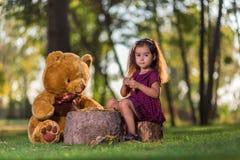 Menina que joga com um urso de peluche Fotografia de Stock Royalty Free