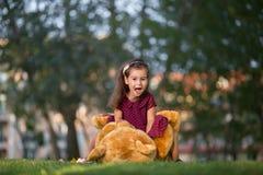 Menina que joga com um urso de peluche no parque Imagem de Stock Royalty Free