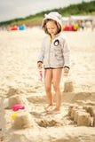 Menina que joga com uma boneca na areia na praia Fotografia de Stock
